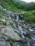 A powerful mountain stream flows down from the rocks and stones stock photography