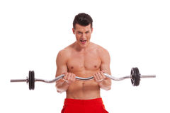 Powerful muscular man with a barbell in hands Royalty Free Stock Image