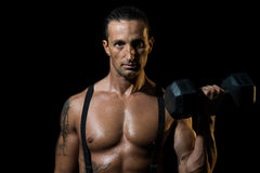 Powerful muscular man lifting weights Stock Photography