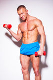 Powerful muscular man lifting weights. Royalty Free Stock Images