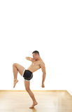 Powerful muscular sports guy standing in fight position kicking Royalty Free Stock Photography