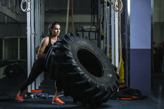 Powerful muscular woman CrossFit trainer doing tire workout at gym stock photography