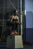 Powerful muscular woman CrossFit trainer jumps during workout at gym stock image