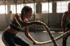 Woman doing battle rope workout at gym. Powerful muscular women exercising with battle ropes at the gym with personal trainer. Battle rope workout at gym with stock photos