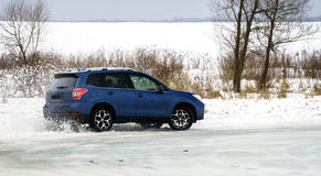 Powerful offroader car sliding by lake ice Royalty Free Stock Photos