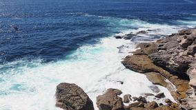 Pacific Ocean waves Crashing Onto Rocks, Australia. Powerful Pacific Ocean waves rolling and crashing on to sandstone rocks at the base of South Head cliffs stock video footage
