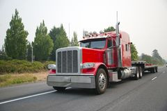 Powerful red big rig semi truck with flat bed step down semi trailer move on smog road for loading cargo. Powerful red big rig semi truck with flat bed step down stock photo