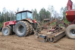 A powerful red diesel tractor with a connected sowing unit, a combine with large wheels plows the land, sows crops, performs agrar. Ian, farm work on the Royalty Free Stock Photo