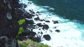 Powerful sea waves breaking to rocky island. Turquoise ocean waves splashing to stony cliff with foam and spray while. Storm. Mountain cliff and sea landscape stock video