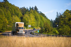 Powerful semi truck cornering scenic highway. Large spectacular classic bonnet brown truck with trailer cornering scenic winding road in Columbia Gorge on a Royalty Free Stock Photography