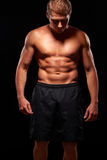 Powerful shirtless muscular man looking down, isolated on  black Stock Photography