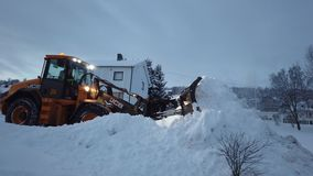 Powerful snowplough clearing parking lot. In Tromso town in winter, Norway stock video