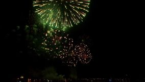 Fireworks explode with multi-colored lights in dark sky. Powerful sparks of festive firecracker illuminate night sky. Amazing festive fireworks explode with stock video