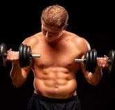 Powerful sportsman doing exercises for biceps with dumbbells on black. Powerful shirtless muscular sportsman pumping up biceps muscles with dumbbells, dressed in Royalty Free Stock Image