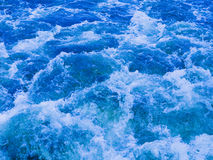 Powerful stream of vibrant blue water Stock Photos