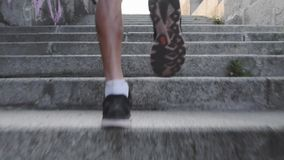 Powerful strong male legs running up stairs. Athletic slim tanned legs runs up steps. Close up back view of muscular male legs. Yo
