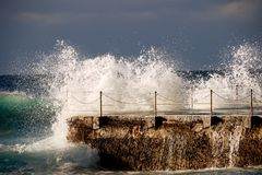 Powerful Stunning Wave Crashing Against Outdoor Pool. Stock Photos