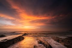 Powerful Sunset with a dramatic sky in the region Alentejo, Portugal. Powerful Sunset with a dramatic sky and rocks in the foreground at the Atlantic Ocean royalty free stock photo