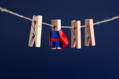 Powerful super hero conceptual photo with superstar clothespin character in blue suit red cape. leadership and wooden. Clothespins team at work. Dark blue royalty free stock photo