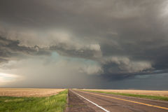 A powerful supercell thunderstorm looms over the highway. Royalty Free Stock Photography