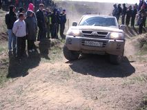 Powerful SUV overcome a rocky slope at the races the crowd of people, the audience watching the spectacle royalty free stock photography