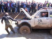 Powerful SUV overcome a rocky slope at the races the crowd of people, the audience watching the spectacle stock photos