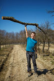 Powerful teenager raising a tree trunk in an orchard. Powerful teenager raising a cut tree trunk with one arm in an orchard on springtime Stock Photo