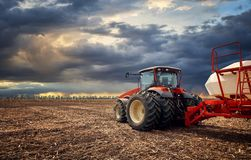 A powerful tractor works in the field. Tractor working on the farm, a modern agricultural transport, a farmer working in the field, fertile land, tractor on a Stock Photo