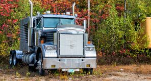 Powerful truck surrounded by foliage trees, New England.  Royalty Free Stock Photos