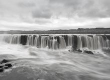 Black and white long exposure image of Selfoss waterfall on Jokulsa a Fjollum river in Iceland. Powerful water stream falling to abyss from high to river stock photos