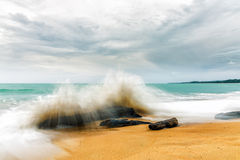 Powerful wave is splashing to old timber on the beach at evening of rainy day Royalty Free Stock Images
