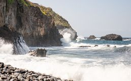 Powerful waves break on rocks in the sea stock images