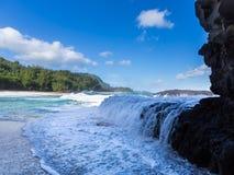 Powerful waves flow over rocks at Lumahai Beach, Kauai. Dramatic powerful waves crash over rocks on dangerous beach at Lumaha'i, Kauai, Hawaii Royalty Free Stock Image