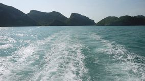 Powerful waves pulled out from fast moving boat, a huge stream of deep blue water with white foam rising up on beautiful. Islands on the background. slow motion stock video footage