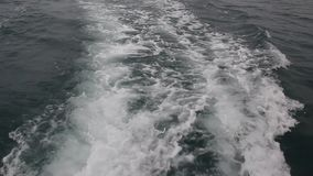 Wake of speed boat. Powerful waves pulled out from fast moving boat, a huge stream of deep  water with white foam rising up stock video
