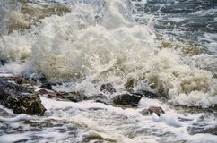 Powerful waves of the sea foaming, breaking against the rocky shore royalty free stock photo