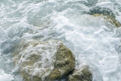 Powerful waves of the sea foaming, breaking against the rocky shore. sea textured. Athens, Greece stock photo