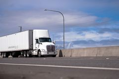 Powerful white day cab big rig semi truck with roof spoiler tran. Powerful white day cab American made big rig semi truck with roof spoiler to improve Royalty Free Stock Photo