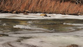 Powerful winds gust over a partially frozen river stock video footage