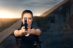Powerful Woman Aiming Gun Action Movie Style. Portrait of a girl in a heroine cosplay  costume pointing gun at the camera Stock Images