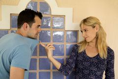Powerful woman controls her boyfriend by pulling his t-shirt Stock Images