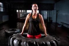 Powerful woman lifting big tire at intense training. Strong fit woman at gym stock image