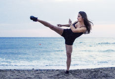 Powerful woman performing martial arts kick. On the beach at sunrise working out Stock Photo