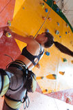 Powerful woman training hard in climbing gym Stock Photo