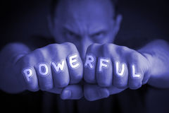 POWERFUL written on an angry man's fists. POWERFUL written on the fingers of an angry man's fists. Blue colored. Message concept image Stock Image