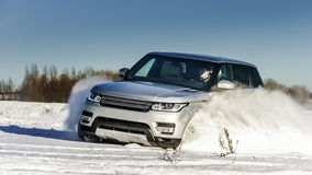 Powerful 4x4 offroader car running on snow field Stock Image