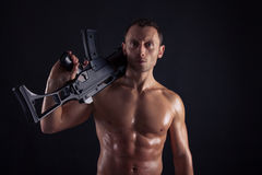 Powerful young man with rifle. Powerful young man with assault rifle Royalty Free Stock Photography