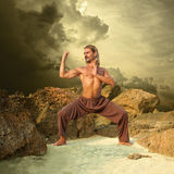 Powerful Young Man Trains in Karate. Cloudy Background royalty free stock photos