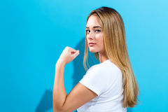 Powerful young woman. On a blue background Stock Photo