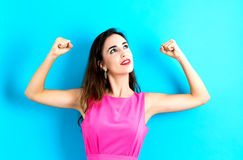 Powerful young woman. On a blue background Stock Images